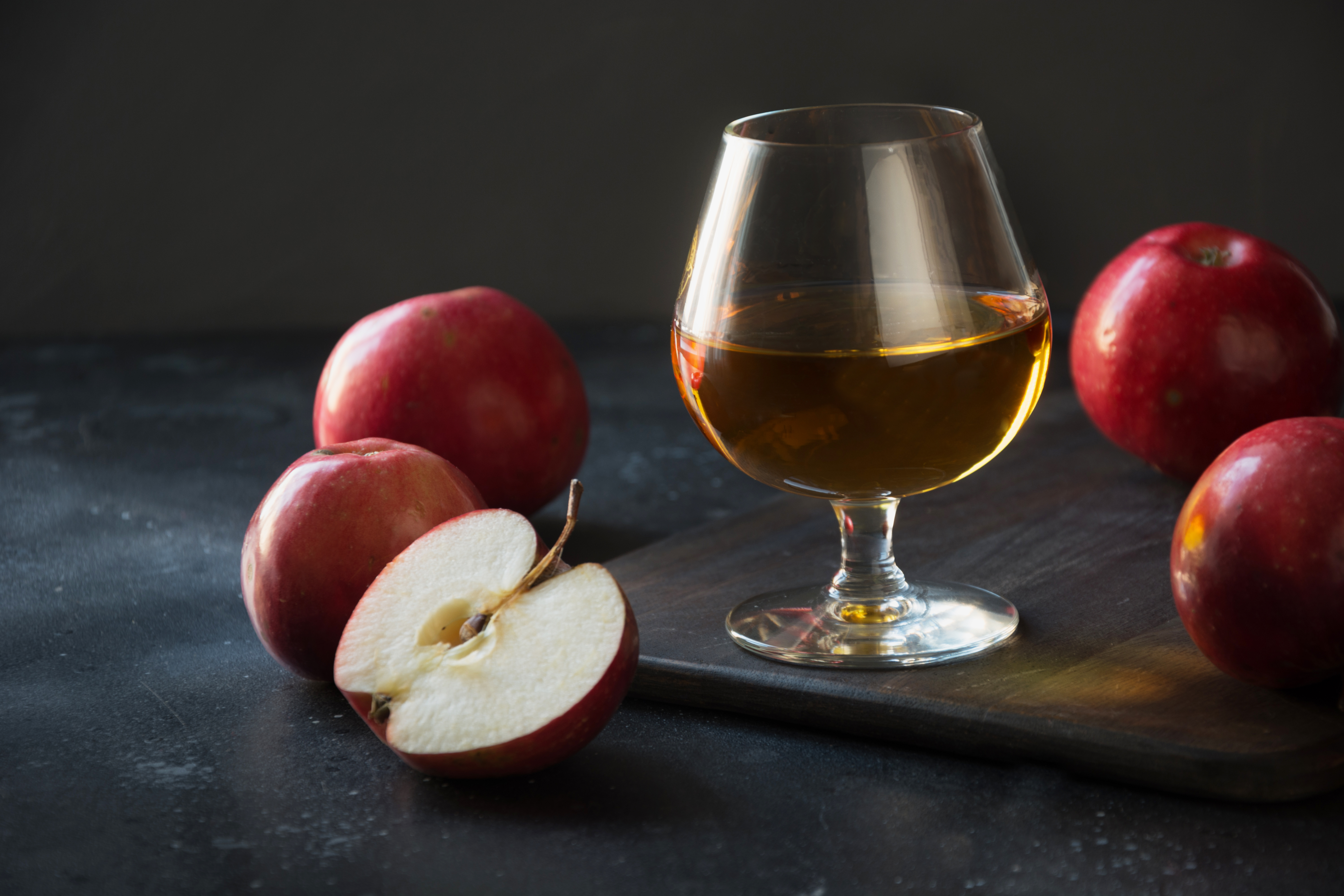 Glass,With,Calvados,Brandy,And,Red,Apples,On,Black.,Close