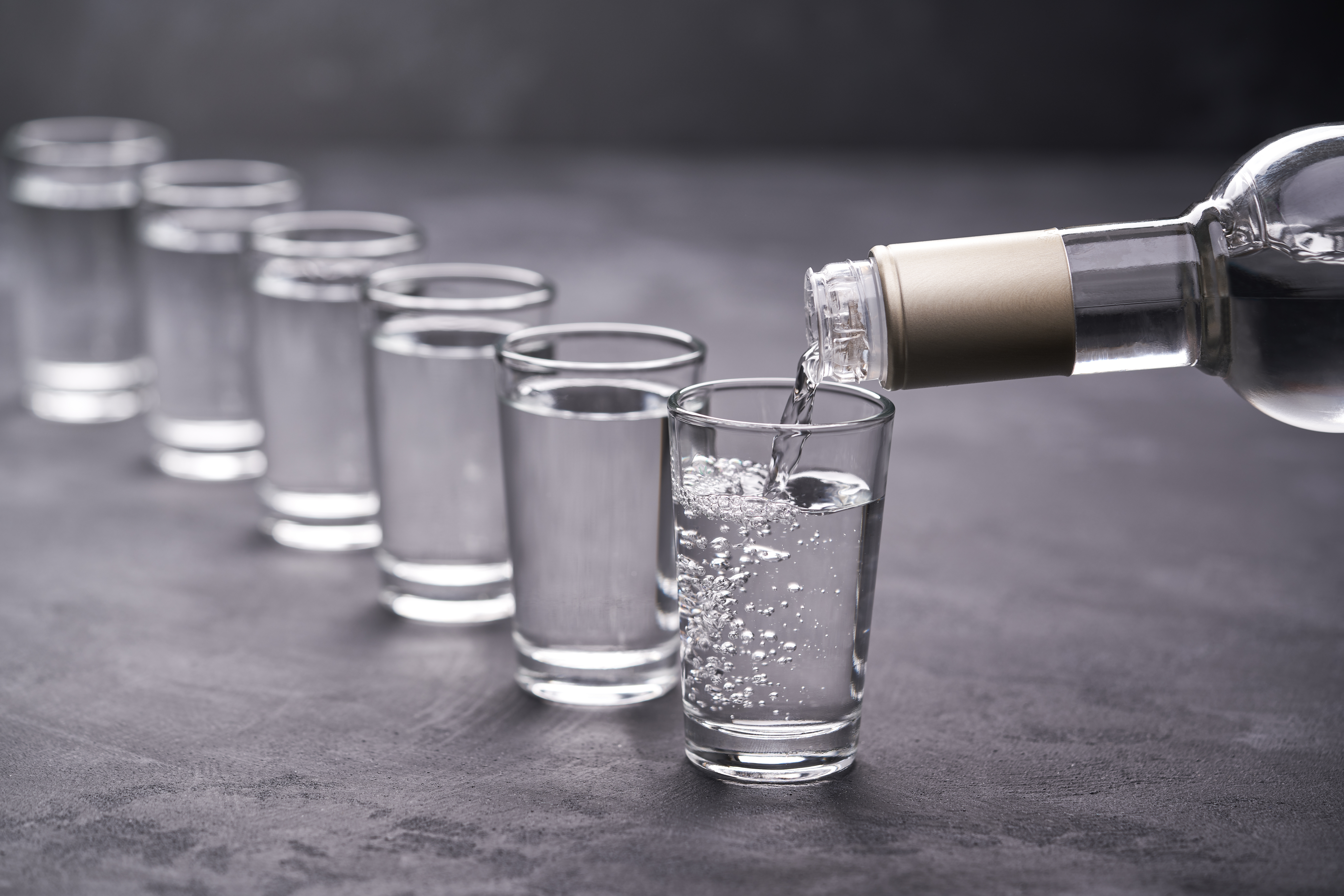 Pouring,Vodka,Into,The,Glass,On,A,Black,Background,,Selective